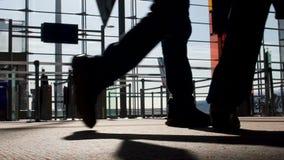 Hombres que caminan a través de la terminal iluminada por el sol con las maletas, embarque plano almacen de video