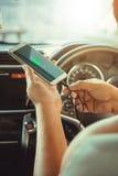Hombres que cargan los teléfonos elegantes en el coche Foto de archivo libre de regalías