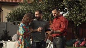 Hombres que comunican en jardín almacen de video