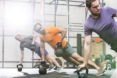 Hombres que ejercitan con los kettlebells en gimnasio del crossfit Fotos de archivo