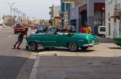 Hombres que empujan un coche del vintage en Malecon en La Habana fotografía de archivo