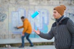 Hombres que escriben la pintada y que juegan con la poder de espray imagenes de archivo