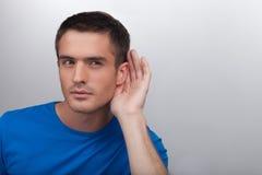 Hombres que escuchan detras de las puertas. Chismes que escuchan hermosos de los hombres jovenes mientras que st Imagenes de archivo