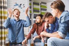 Hombres que juegan al ganador del juego de póker junto en casa foto de archivo libre de regalías