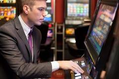 Hombres que juegan en el casino en las máquinas tragaperras fotografía de archivo libre de regalías