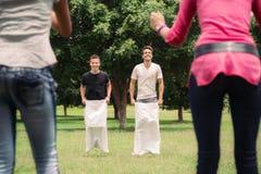 Hombres que juegan la raza de saco con animar de las novias Foto de archivo libre de regalías