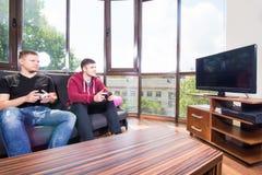 Hombres que juegan a los videojuegos mientras que se sienta en el sofá Fotografía de archivo