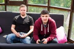Hombres que juegan a los videojuegos mientras que se sienta en el sofá Imagen de archivo libre de regalías
