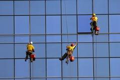 Hombres que lavan ventanas en la altura Foto de archivo libre de regalías
