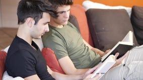 Hombres que leen los libros de texto en el sofá almacen de metraje de vídeo
