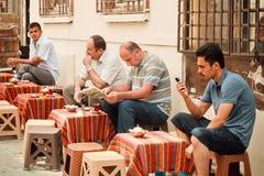 Hombres que leen noticias y que beben té en café al aire libre tradicional de la capital turca Imagen de archivo
