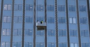Hombres que limpian Windows de cristal en el alto edificio de la subida metrajes