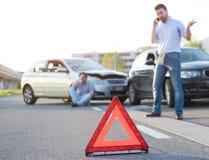 Hombres que llaman los primeros auxilios después de un mún choque de coche en el camino Imagen de archivo