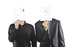 Hombres que llevan a cabo las mascarillas de papel Fotografía de archivo