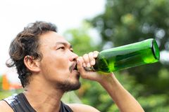 Hombres que llevan a cabo verde de la botella de cerveza fotografía de archivo libre de regalías