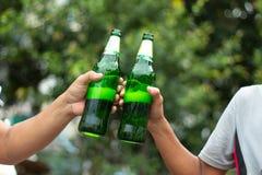 Hombres que llevan a cabo verde de la botella de cerveza foto de archivo libre de regalías
