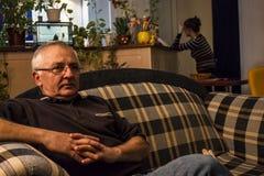 Hombres que localizan en un sofá Fotos de archivo libres de regalías