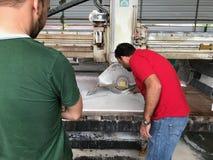 Hombres que manchan la máquina del cortador de cerámica de la teja para la construcción Imagenes de archivo