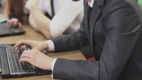 Hombres que mecanografían en los teclados del ordenador portátil en oficina metrajes