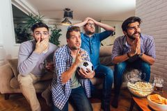 Hombres que miran deporte en el griter?o de la TV junto en casa alegre imagenes de archivo