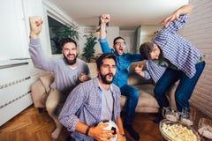 Hombres que miran deporte en el griter?o de la TV junto en casa alegre fotografía de archivo libre de regalías