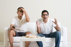 Hombres que miran el partido de fútbol en la TV en casa Foto de archivo libre de regalías