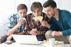 Hombres que miran el vídeo en el ordenador portátil Imagenes de archivo