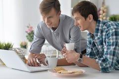 Hombres que miran el vídeo en el ordenador portátil Imágenes de archivo libres de regalías