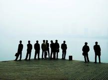 Hombres que miran hacia fuera sobre el lago Foto de archivo