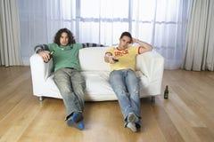 Hombres que miran la televisión en el sofá  Fotos de archivo