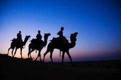 Hombres que montan el camello a través oscuro del desierto del Lit Imagen de archivo libre de regalías