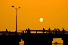 Hombres que montan las bicicletas en el puente, puesta del sol Fotos de archivo