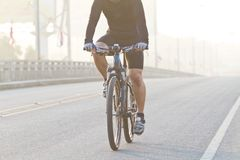 Hombres que montan las bicicletas en la neblina del puente Imagenes de archivo