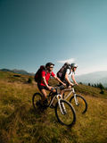 Hombres que montan las bicis de montaña imagenes de archivo