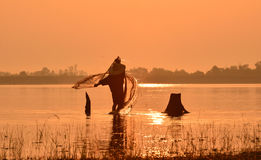 Hombres que pescan en silueta un barco de pesca Imagen de archivo