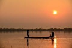 Hombres que pescan en silueta una pesca Imagenes de archivo