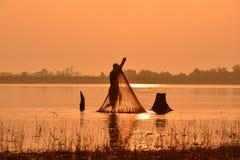 Hombres que pescan en silueta una pesca Fotografía de archivo