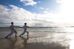 Hombres que practican karate en la playa Imagen de archivo