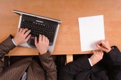 Hombres que preparan el contrato - en la computadora portátil y el papel Fotos de archivo libres de regalías