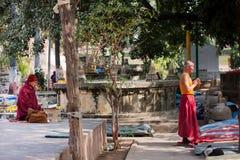Hombres que ruegan en un parque cerca del templo budista Fotos de archivo libres de regalías
