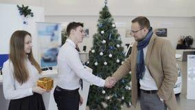 Hombres que sacuden las manos en concesión de coche hermosa en el fondo del árbol de navidad metrajes