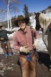 Hombres que se colocan con el caballo y la sonrisa Fotos de archivo