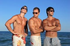 Hombres que se relajan en la playa Fotografía de archivo libre de regalías
