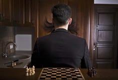 Hombres que se sientan cómodamente contra un tablero de ajedrez Fotografía de archivo libre de regalías