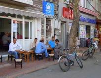 Hombres que se sientan en el café del pavimento Imágenes de archivo libres de regalías
