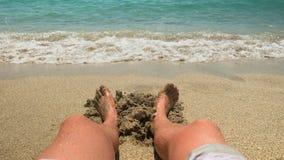 Hombres que se sientan en playa Fotografía de archivo