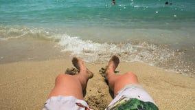 Hombres que se sientan en playa Foto de archivo