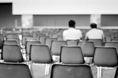 Hombres que se sientan en sillas vacías Imagen de archivo libre de regalías