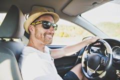 Hombres que se sientan en un coche de alquiler en vacante del día de fiesta con las gafas de sol imagen de archivo libre de regalías