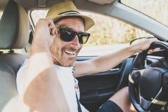 Hombres que se sientan en un coche de alquiler en vacante del día de fiesta con las gafas de sol foto de archivo libre de regalías